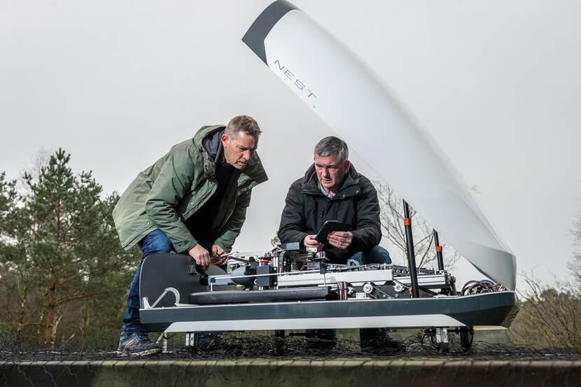 Kalkhoven en Swanenberg inspecteren in 't Harde een drone van het merk Nest.